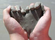 Childâs entrega a areia da terra arrendada dada forma como o coração Fotografia de Stock Royalty Free