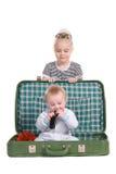 ChildÑ som sitter i en gammal grön resväska royaltyfri bild