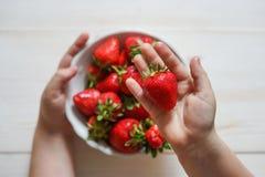 Child& x27 φράουλα εκμετάλλευσης χεριών του s στο αγροτικό συγκεκριμένο υπόβαθρο Έννοια θερινής υγιής κατανάλωσης Τοπ όψη στοκ φωτογραφία