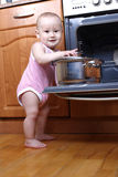 Child 1 year old in the kitchen cooking breakfast Royalty Free Stock Photos