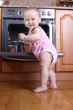 Child 1 year old in the kitchen cooking breakfast Stock Photos