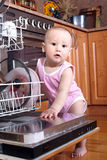 Child 1 year old in the kitchen at dishwasher Royalty Free Stock Photo