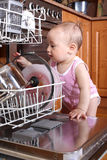 Child 1 year old in the kitchen at dishwasher Stock Image
