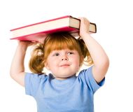 Child. Portrait of young smiling child holding textbook over her head Stock Photo