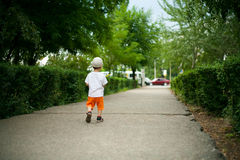 Child. In loneliness goes on road from park stock image