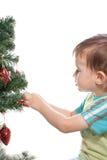 Child. Decorating christmas tree isolated on white background stock image