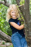 Child. A vertical picture of a happy and smiling young blond haired and blue eyed girl dressed in blue jeans and a blue t-shirt sitting in a tree Stock Image