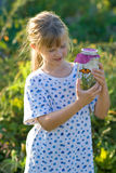 Child. A vertical picture of a young girl observing a viceroy butterfly in a jar stock images