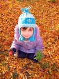 Child. A little girl sits among fallen leaves tree rowan Royalty Free Stock Photo