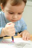 Child. The child draws red pencil Stock Image