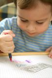 Child. The child draws red pencil Stock Images