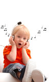 Child of 2 years listening music. In earphones Stock Images