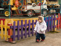 A child. Goes along the fence at the park amusement park Royalty Free Stock Photography