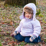 A child. Is sitting on the frosted grass Stock Image