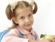 Child 30. Little pretty schoolgirl with blue satchel and apple Stock Photos