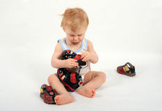 Child. The beautiful little boy tries on footwear Royalty Free Stock Photo