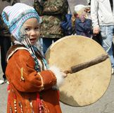 Child. The Small child on national fabrics knocks on percussion instrument Stock Images