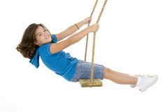 Cute Caucasian child playing on a wooden swing