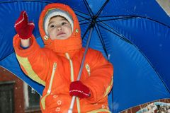 Child. In red overalls on background of the blue umbrella Stock Image