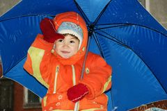 Child. In red overalls on background of the blue umbrella Royalty Free Stock Image