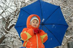 Child. In red overalls on background of the blue umbrella Stock Photo