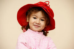 Child. In red hat on background wall Stock Image