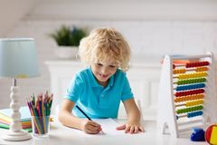 Child with abacus doing homework after school. Child doing homework at home. Little boy with wooden colorful abacus doing math exercise learning addition and royalty free stock image