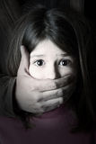 Child abduction. Scared young girl with an adult man's hand covering her mouth Stock Photos
