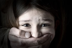 Child abduction. Scared young girl with an adult man's hand covering her mouth Stock Images