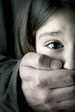 Child abduction. Scared young girl with an adult man's hand covering her mouth Stock Image