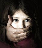 Child abduction. Scared young girl with an adult man's hand covering her mouth Royalty Free Stock Photography