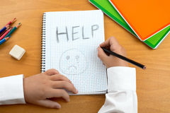 Child abuse. An image /poster covering the Social Issues of child abuse, schoolchild in uniform at a desk asking for help by a written message saying Help with a Stock Photos