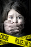Child abuse. Scared young girl with an adult man's hand covering her mouth Royalty Free Stock Photos