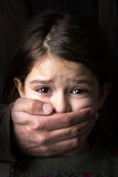 Child abuse. Scared young girl with an adult man's hand covering her mouth Royalty Free Stock Photography