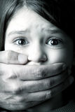 Child abuse. Scared young girl with an adult man's hand covering her mouth Stock Photo