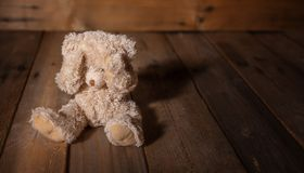 Child abuse.Teddy bear covering eyes, dark empty background, copy space royalty free stock images