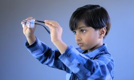 Child in act of wearing glasses royalty free stock photos