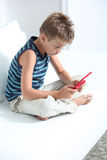 Child addiction to video games. Little boy playing video games on sofa Royalty Free Stock Image