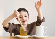 Child adding honey in cup of tea Stock Photos