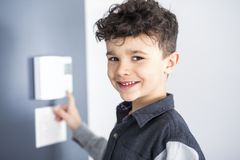Child Adjusting Thermostat On Central Heating Control Stock Image