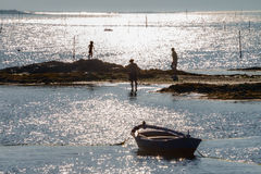 A child, an adult and an elderly. In a beach at sunset with a boat. Stages of life Royalty Free Stock Photography