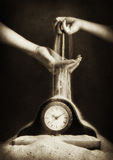 Child and adult hand with sand and clock Stock Photos