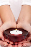 Child and adult hands holding candle Stock Photos