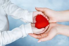 Child and adult hands are holding a heart together royalty free stock images