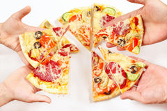 Child and adult hands with pieces of pizza Stock Photography