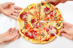 Child and adult hands take pieces of flavored pizza Stock Images