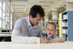 Child and adult in library. Child pupil with parent or teacher reading a book in public library Stock Image