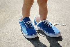 Child in adult's blue shoes. Baby foot stepping into big shoes to fill Stock Photos