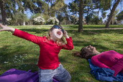 Child with adult sunglasses singing in park royalty free stock photography
