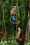 Child in adventure park. Young boy climbing a rope way in an adventure park Royalty Free Stock Photos
